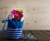 Small bouquet in knitted vase — Stock Photo
