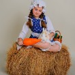 Girl in the hay feeding the Easter Bunny carrots. — Stock Photo #69311643