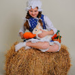 Girl in the hay feeding the Easter Bunny carrots. — Stock Photo #69311683