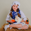 Girl in the hay feeding the Easter Bunny carrots. — Stock Photo #69311835