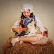 Girl in the hay feeding the Easter Bunny carrots. — Stock Photo #69346273