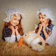 Girl in the hay feeding the Easter Bunny carrots. — Stock Photo #69388445