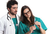 Young bearded orthopedic doctor and female surgeon with syringe. Caucasian. Isolated on white. — Stock Photo
