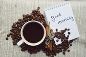 A hot Cup of coffee,coffee beans, Notepad, cinnamon, spices — Photo