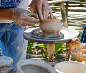 Hands working on pottery wheel , close up — Stock Photo