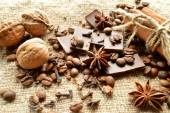 Cinnamon, chocolate, coffee, cloves, hazelnuts walnuts on sacking background — Stock Photo