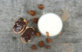 Cup of hot milk with cinnamon , Spices and hazelnuts, walnuts, closeup on wooden background — Stok fotoğraf