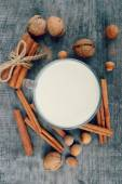 Cup of hot milk with cinnamon , Spices and hazelnuts, walnuts, closeup on wooden background — Foto Stock