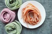 Colorful raw italian pasta on wooden background — Stock Photo