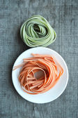 Colorful raw italian pasta on wooden background — Stockfoto