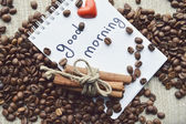 A hot Cup of coffee,coffee beans,Notepad,cinnamon,spices — Fotografia Stock