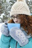 黑头发的女孩穿着一件绿松石的夹克、 身体具绵状毛的帽子和淡蓝色的围巾,在公园里读书,饮用茶、 咖啡、 可可 — 图库照片