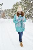 黒髪の少女は、公園で本を読んで、紅茶、コーヒー、ココアを飲むターコイズ ブルー ジャケット、身体毛糸の帽子、光の青いスカーフに身を包んだ — ストック写真