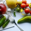 Vegetables and fruits for weight loss with a measuring tape and fork — Stock Photo #66126609