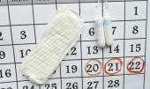 Frau-Hygiene-Schutz, schließen-up.menstruation Kalender mit Wattepads Tampons, orange Gerber, Sanitär auf rotem Grund — Stockfoto