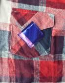 Latex condom on shirt background — Stock Photo