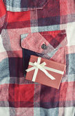 Gift box  on a red plaid button up style shirt — Stock Photo