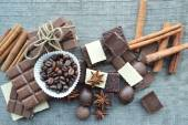 Bar of chocolate, coffee beans, hazelnuts, walnuts, cinnamon, coriander, spices .chocolate bar, candy bars,  different chocolate sweets on a wooden background — Stock Photo