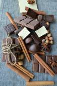 Bar of chocolate, coffee beans, hazelnuts, walnuts, cinnamon, coriander, spices .chocolate bar, candy bars,  different chocolate sweets on a wooden background.big choice of various sweets — Foto Stock