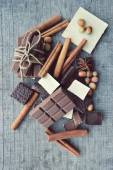 Bar of chocolate, coffee beans, hazelnuts, walnuts, cinnamon, coriander, spices .chocolate bar, candy bars,  different chocolate sweets on a wooden background.big choice of various sweets — Foto de Stock