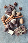 Bar of chocolate, coffee beans, hazelnuts, walnuts, cinnamon, coriander, spices .chocolate bar, candy bars,  different chocolate sweets on a wooden background.big choice of various sweets — Stock Photo