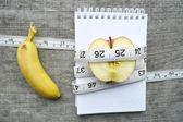 Boş defter ile muz ve elma ve ölçüm bandı — Stok fotoğraf