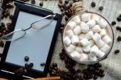 Marshmallows in bowl with Ebook and glasses, candies and coffee beans — Stock Photo