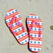 Red white and blue flip flops on the sand. Perfect for cover art — Stock Photo #65213371