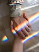 Hand in hand with rainbow symbolizing sentimental bond — Stock Photo