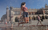 Yuoth seeking escape from the summer heat in Main Square in Cracow, Poland — Stock Photo