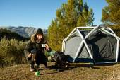 Man camping drinking coffee near tent smiling happy outdoors in  — Stock fotografie