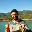 Beautiful bearded man hiker smiling happy  eating an apple durin — Stock Photo #70181971