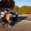 Young man sits near car talking on cell phone because his auto b — Stock Photo #70182625