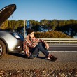 Young brutal man sits near car talking on cell phone because his — Stock Photo #70182689