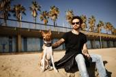 Strong bearded man in sunglasses sitting in sand with friend dog — Stock Photo