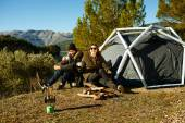Couple camping drinking coffee near tent smiling happy outdoors — Stock Photo