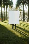 A man holding a empty blank white paper poster or board at city backgound — Stock Photo
