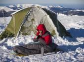 Een man zit in een slaapzak in de buurt van de tent. — Stockfoto