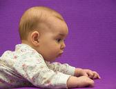Baby op een paarse achtergrond. — Stockfoto