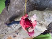 Girl climbing up a cliff. — Stock Photo