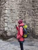 Ein junges Mädchen mit einem Rucksack Aufnahmen des Telefons. — Stockfoto
