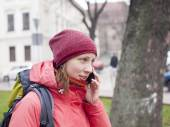 A young girl with a backpack and phone. — Stock Photo