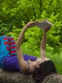 Menina lendo um livro ao ar livre. — Fotografia Stock