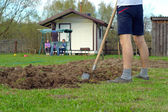 Young man digging the earth — Stock Photo