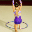Girl gymnast performs with a Hoop at the competition — Stock Photo #76611143