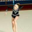 Girl gymnast performs with a Hoop at the competition — Stock Photo #76611145
