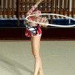 Girl gymnast performs with a Hoop at the competition — Stock Photo #76611155