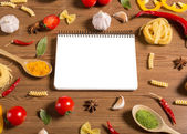 Notebook for recipes, vegetables and spices on wooden table — Stock Photo