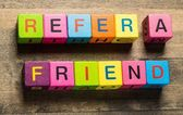 Refer. Tablet pc with text Refer a Friend with blue background — Stock Photo