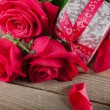 Day. Red roses and holiday gift on a wooden table — Stock Photo #71268275